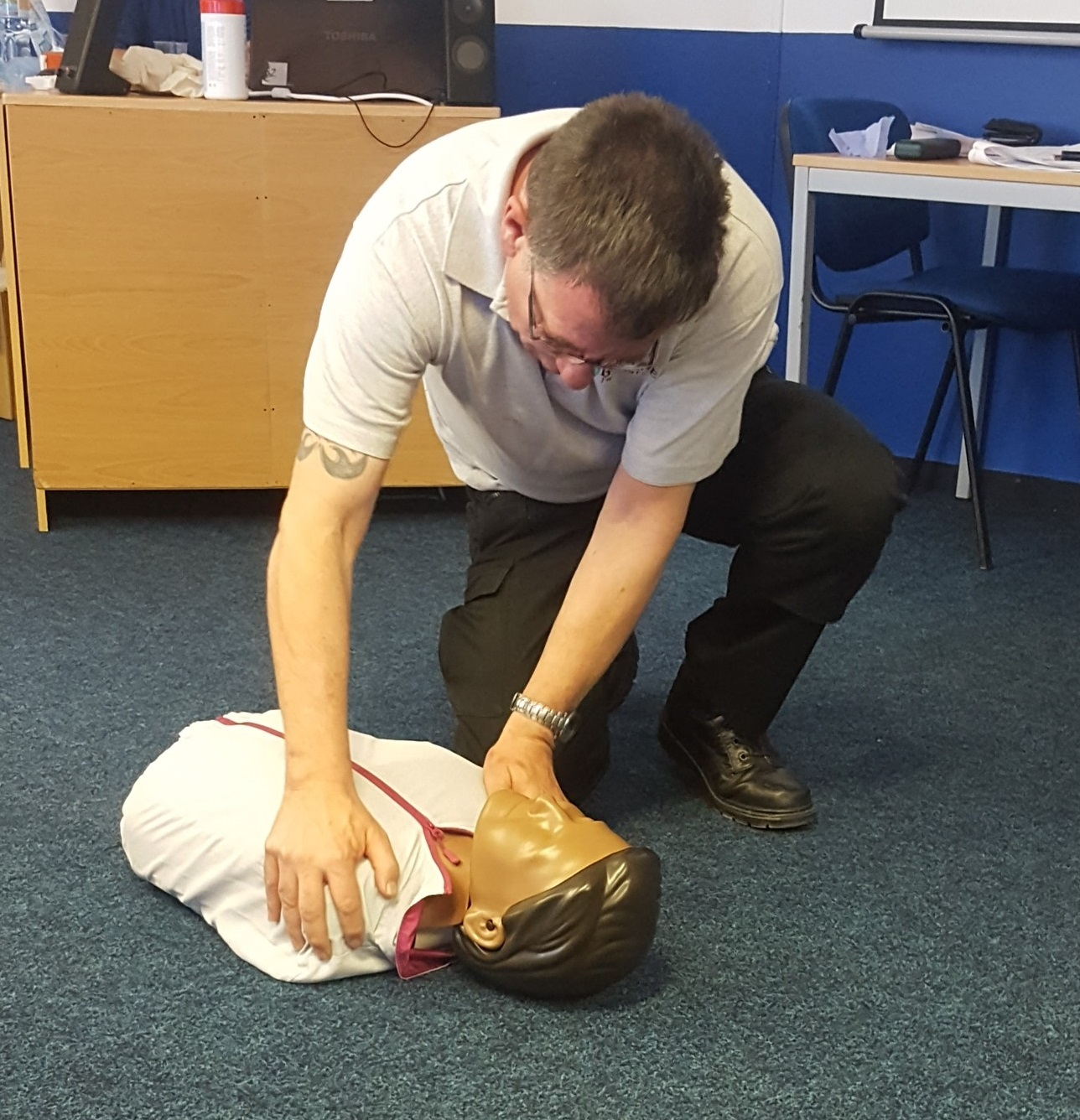 Man showing CPR technique on a dummy