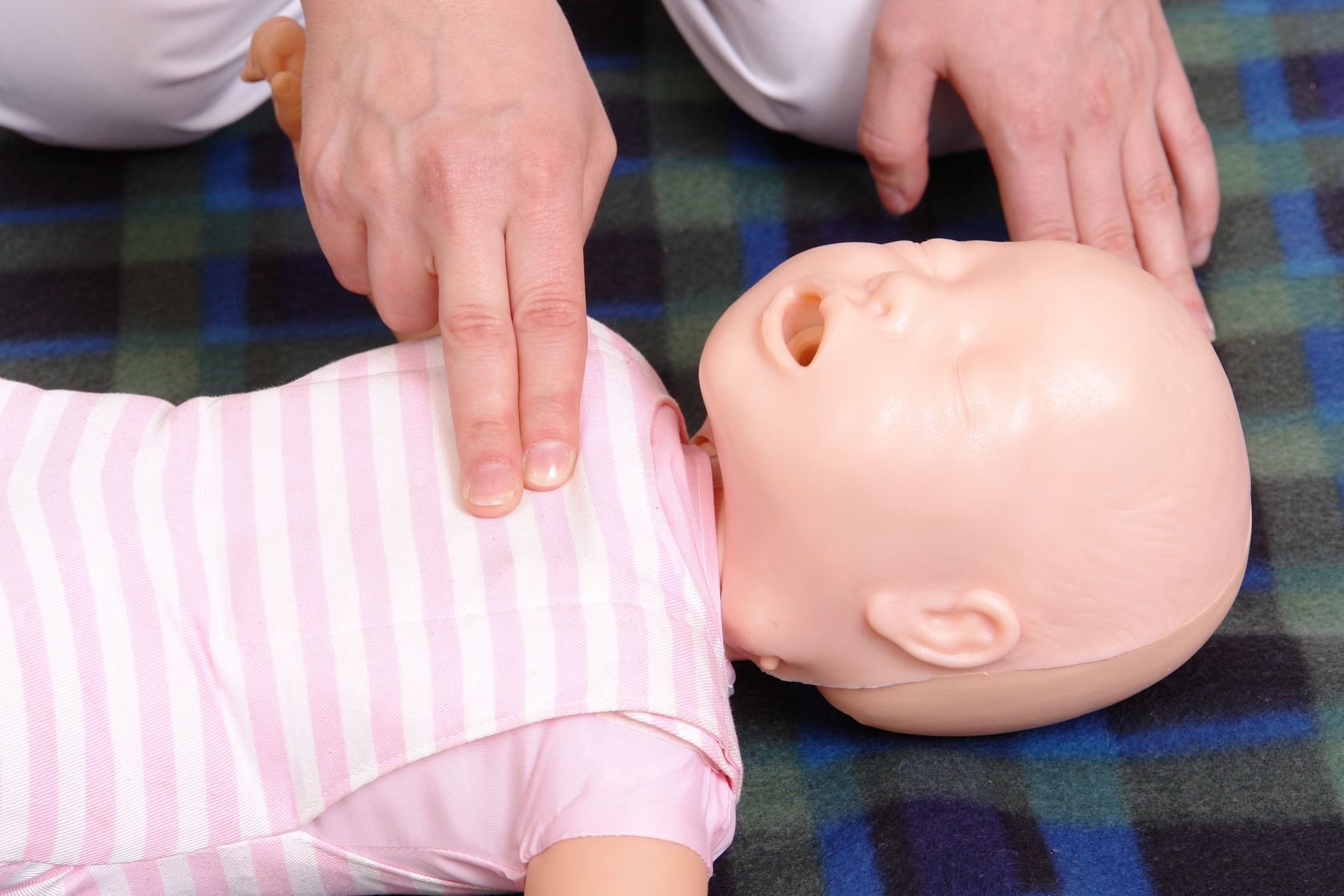Performing CPR on a baby dummy